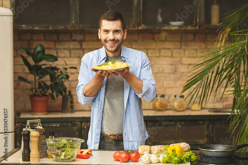 Wall mural It's so delicious! Casual happy young man preparing pasta at home in loft kitchen and smiling.