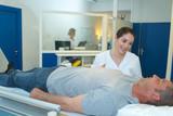 nurse examining the patient before xray examination - 230476995