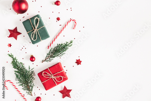 Leinwandbild Motiv Christmas composition. Gifts, fir tree branches, red decorations on white background. Christmas, winter, new year concept. Flat lay, top view, copy space