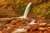Autumn mountain waterfall stream in the rocks with colorful red fallen dry leaves, natural seasonal background