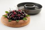 Bizcocho rellleno de frambuesas y cerezas junto a un molde savarín