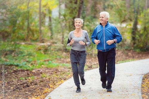 Leinwanddruck Bild Smiling senior active couple jogging together in the park