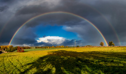 A stunning rainbow against dark clouds over rural fields in Suffolk, UK