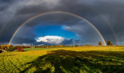A stunning rainbow against dark clouds over rural fields in Suffolk, UK © Rob