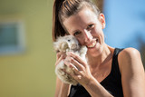Smiling woman looking at camera holding baby rabbit in her hands