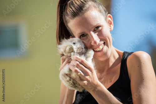 Smiling woman looking at camera holding baby rabbit in her hands - 230515975