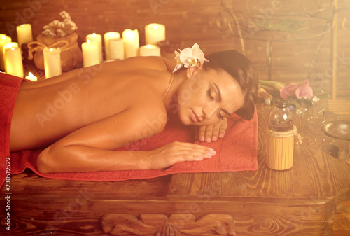 Leinwanddruck Bild Massage Filipino of woman in spa salon. Girl candles in massage spa salon. Sun flare luxary interior in oriental therapy. Dry flowers in clay vases. Color tone on shiny sunlight background.