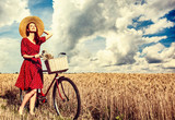 Redhead girl with bicycle on wheat field. - 230524965