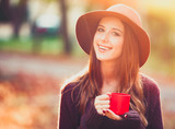 Beautiful redhead girl with cup in the park. - 230525112