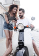 Happy young couple having summer trip on a scooter