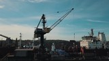 Drone flying around crane while loading cargo ship in shipyard - 230537538
