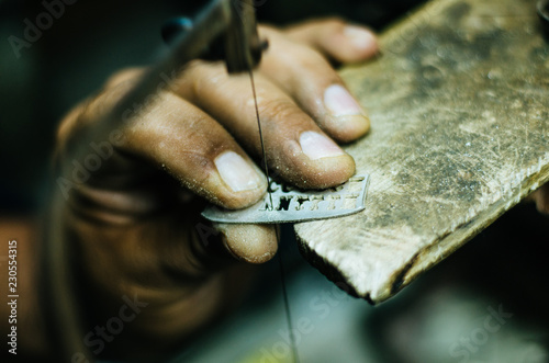 man's hands goldsmith work on a piece of silver with a metal saw on the work table, close up, selected focus, narrow depth of field © Peruphotoart