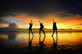 three woman post acting on the beach with golden sunset background