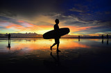 surfer carry a surf board on the beach with golden sunset background