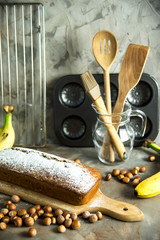 Banana bread is lying on the board among kitchen utensils, bananas and hazelnuts. Homemade bakery concept
