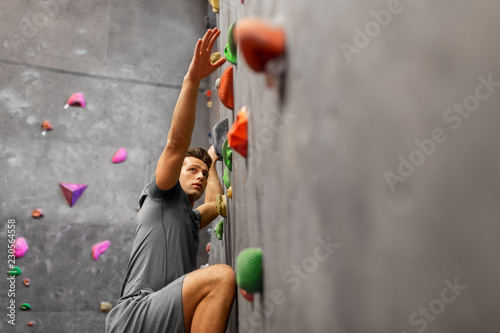 Wall mural fitness, extreme sport, bouldering, people and healthy lifestyle concept - young man exercising at indoor climbing gym