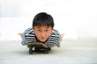 Funny asian boy lying on a skateboard looking to camera