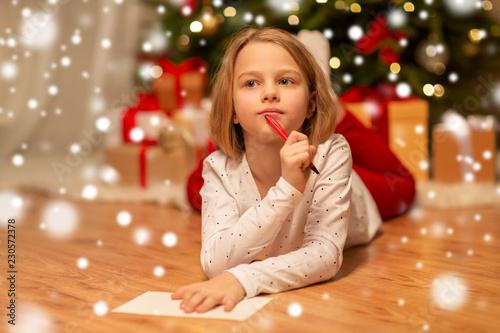 Leinwandbild Motiv christmas, holidays and childhood concept - girl writing wish list or letter to santa at home