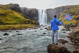 travel to Iceland, tourist holding icelandic flag near scenic waterfall - 230581137