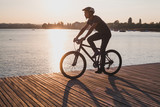 silhouette of man on bicycle in sunset city near lake, sport cycling active leisure - 230581139