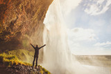 inspiring travel landscape, person standing near beautiful waterfall in Iceland - 230581173