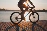 man riding bicycle at sunset, cycling in summer, silhouette of cyclist near the lake - 230581189