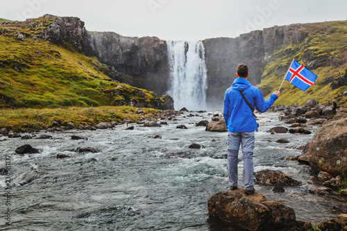 Foto Murales travel to Iceland, tourist holding icelandic flag near scenic waterfall