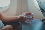 Passenger drinking water in airplane during flight. Close up of hand holding glass in plane. - 230581515