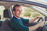 Portrait of happy driver in car. Smiling young man looking at camera who got his driving license. - 230581738