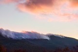 Peaks of green mountains in pink clouds at sunset. White Mountain National Park. USA. New Hamshire.