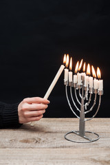 partial view of woman lighting candles on menorah on wooden tabletop on black backdrop, hannukah holiday concept