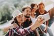 Leinwanddruck Bild - Young Smiling People Sitting in Park taking Selfie