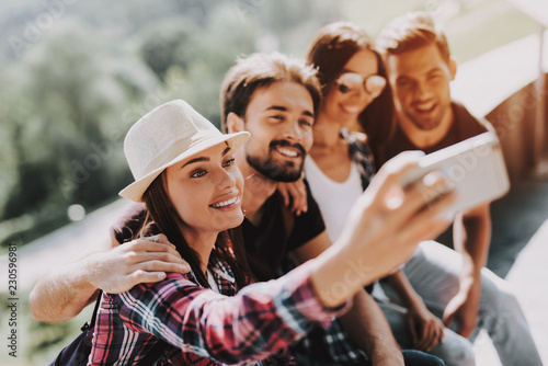 Leinwanddruck Bild Young Smiling People Sitting in Park taking Selfie