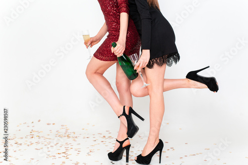 Foto Murales Closeup of legs of women standing on the floor with confetti and having party over white background