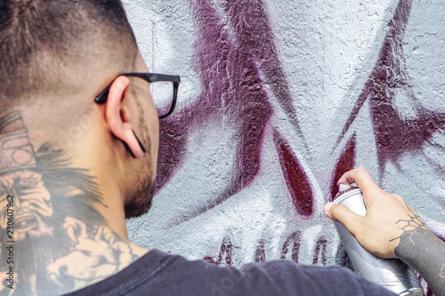 Street graffiti artist painting with a color spray can a dark monster skull graffiti on the wall in the city outdoor - Close up hand paints - Urban, lifestyle contemporary street art concept - 230607962