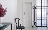 Black wooden chair in white corridor of elegant apartment, real photo with copy space on the white wall