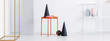 Panoramic view of black cone, pink plate and orange coffee cup on the stylish metal table in white living room interior
