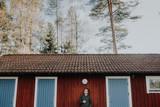 Mann raucht Zigarette vor einem Blockhaus in Schweden - 230613173