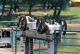 Strong rusted metal gears used to lift and lower metal plate preventing water flow to dam surrounded with protective fence with trees and beach in background on warm summer day - 230622761
