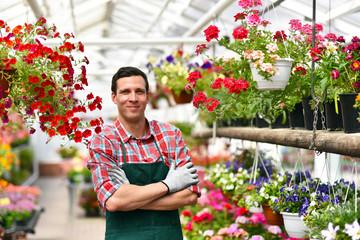 smiling gardener at work in a greenhouse // Portrait lächelnder gärtner bei der Arbeit im Gewächshaus im Blumenhandel