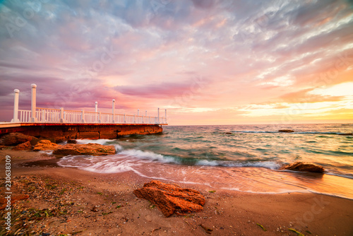 Bright colorful sunrise at the pier by the sea.