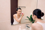 woman is cleaning her face with a brush for deep cleaning - 230639187