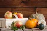 Gifts of autumn: apples in a basket and pumpkins on a wooden background with a copy space