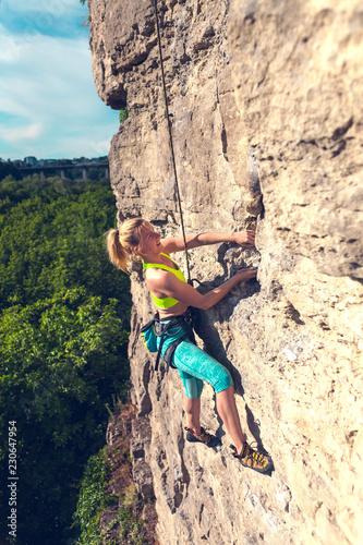 Leinwanddruck Bild The girl climbs the rock.