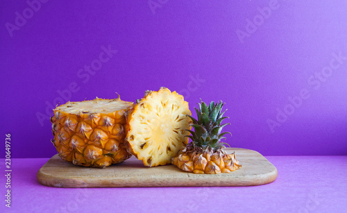Leinwandbild Motiv Slices of ripe juicy pineapple on a cutting board. Macro view yummy exotic fruit on purple background.