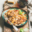 Leinwanddruck Bild - Italian traditional pasta dinner. Tagliatelle bolognese with minced meat, tomato sauce and parmesan cheese and glass of red wine over rustic wooden board, selective focus, square crop