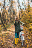 cheerful attractive woman carrying bicycle in yellow autumnal forest - 230651914