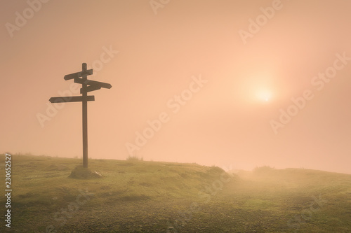 signpost in the mountain at foggy morning