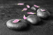Leinwanddruck Bild - Spa stones and flower petals on dark background