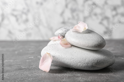 Leinwanddruck Bild Spa stones and flower petals on grey table. Space for text